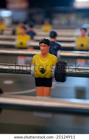 Table soccer player highlighted wearing yellow jersey