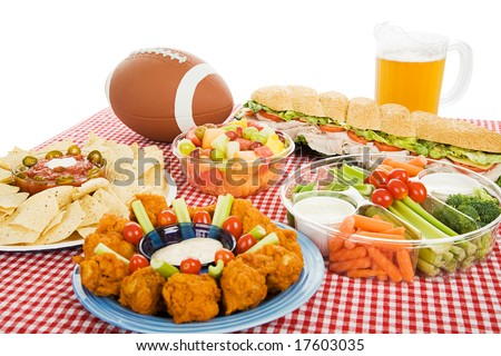 Table spread with appetizer trays for the footbal party.  Horizontal view over white background. - stock photo