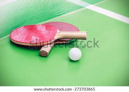 table tennis or ping pong rackets and balls on a green table with net. Focus on the ball - stock photo