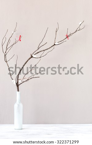 Table top decoration, vase with wooden branch twig with red ribbons, simple elegant rustic holiday festive christmas background - stock photo