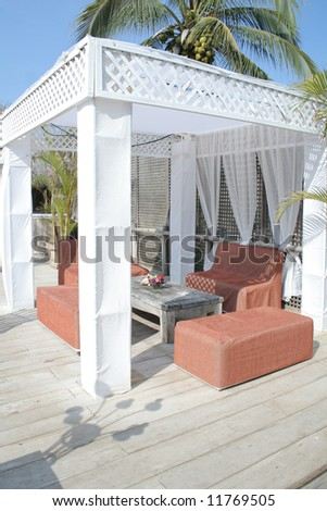 Table under pergola at nice beach front restaurant - stock photo