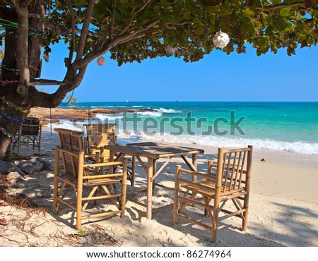 Table under tropical tree on white sand beach