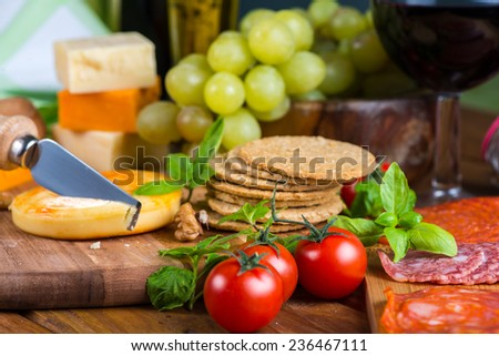 Table view on soft cheese with appetizers and red wine - stock photo