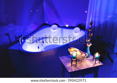 Table with bath products and candles stands near the spa