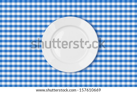 table with blue picnic cloth and plate top view - stock photo