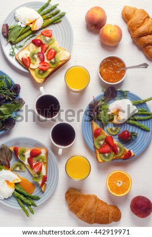 Table with breakfast - asparagus with poached eggs , toast with fruit, croissants, coffee, juice, top view. - stock photo