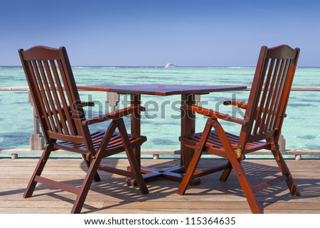 table with chairs in front of a turquoise sea with blue sky