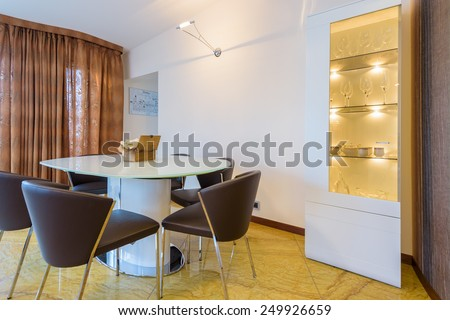 Table with chairs in modern living room interior in luxury apartment, Krakow city, Poland