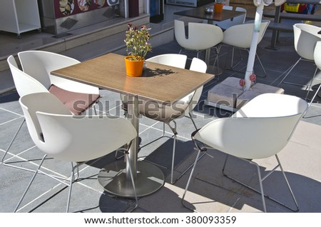 Table with chairs with a wilted rose plant in a pot in outdoors cafe by the sidewalk on sunny day - stock photo