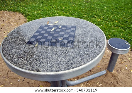Table with chess board and chairs in the city park - stock photo