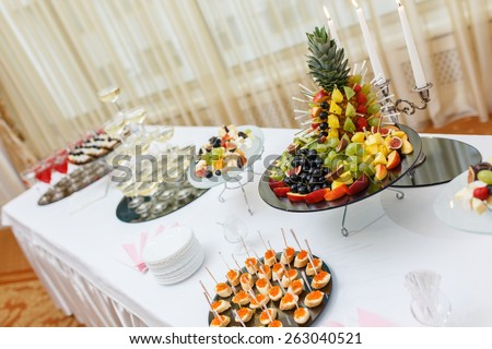Table with cold snacks and tableware on luxury stand-up party - stock photo