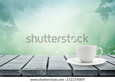 Table with cup of tea in morning fog - stock photo