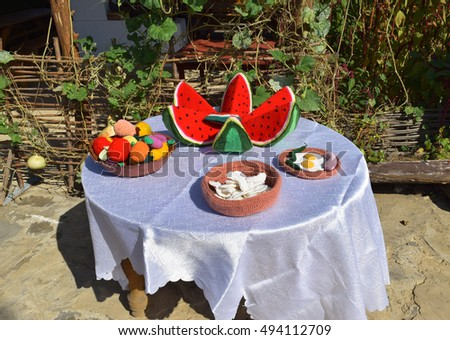 Table with dishes of the knitted fabric. Decorative articles made of knitted things.