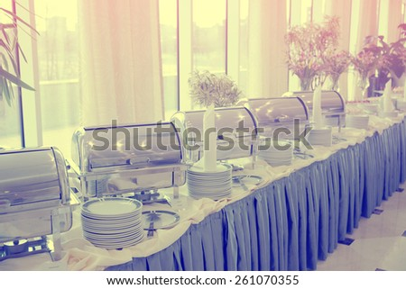 Table with dishware and shiny marmites waiting for guests, toned image - stock photo