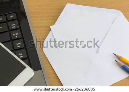 Table with envelope laptop and focus smartphone - stock photo
