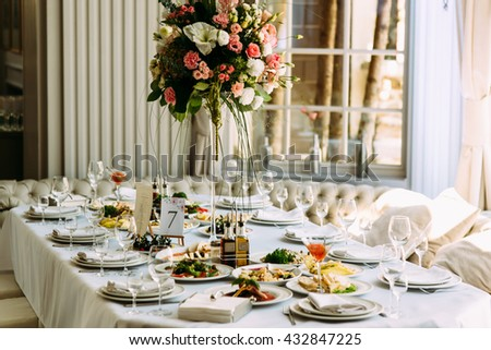 Table with food and flowers on the wedding - stock photo