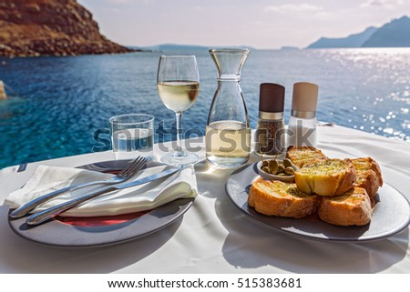 Table with food and wine on the background of the sea