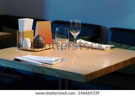 Table with glasses in the cozy cafe with beautiful interior. - stock photo