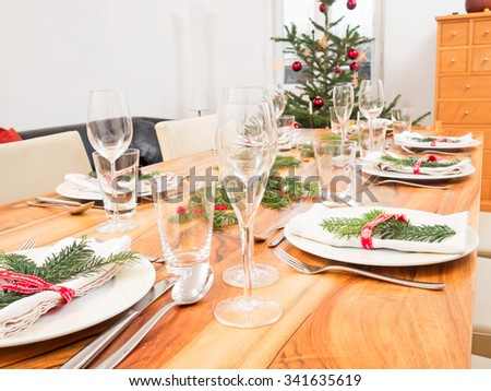 table with glasses, plates, cutlery and Christmas tree - stock photo