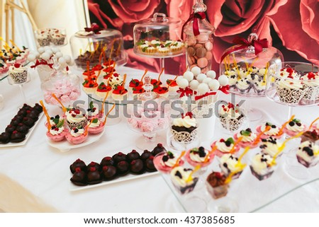 Table with marsh-mallows, macaroons and chocolates stand ready for a festive dinner - stock photo