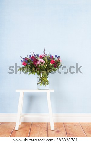 Table with mixed bouquet flowers on blue background - stock photo