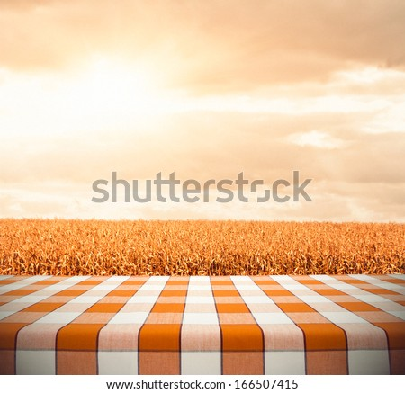 Table with orange tablecloth on cornfield in sunset - stock photo