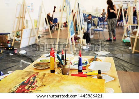 Table with paints in tubes, brushes and paint-roller in art room.