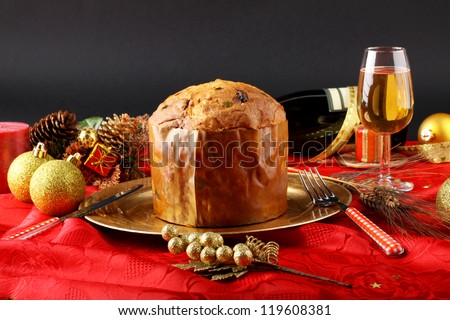 Table with panettone and christmas decorations on complex background