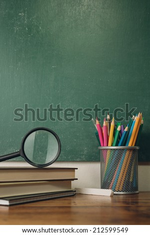 Table with pencils, magnifier and stack of books - stock photo