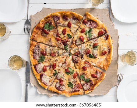 table with pizza set for four persons - stock photo