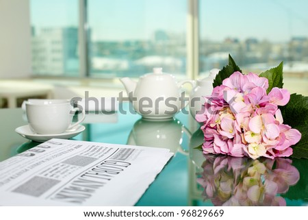 Table with porcelain cup and pot, newspaper and bunch of flowers on it - stock photo