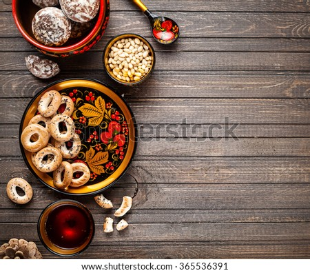 Table with Russian dessert sweet gingerbread and bublik biscuit, wooden spoon painted with floral ornament in the style of Khokhloma at wooden table. Concept of Russian traditional food. - stock photo