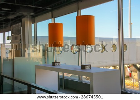 Table with sockets for charging gadgets in airport lounge - stock photo