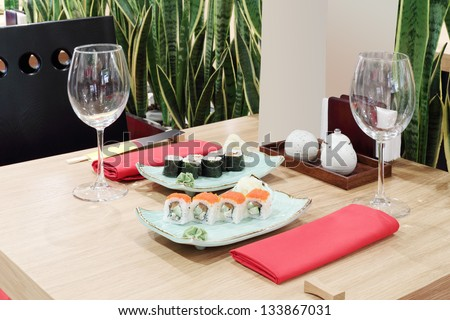 Table with sushi at plates and empty glasses in small modern Japanese restaurant.