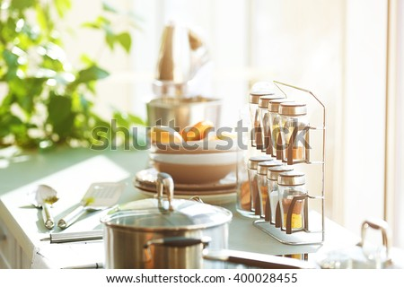 Table with utensils and spices in the kitchen beside window - stock photo
