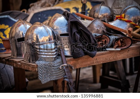 Table with various pieces of medieval armour - stock photo