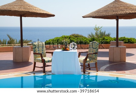 table with wine and fruit near pool - stock photo