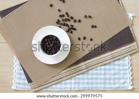 Tablecloth and cup of coffee bean on wooden table - stock photo
