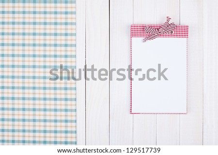 Tablecloth, recipe cook book on white wood background - stock photo