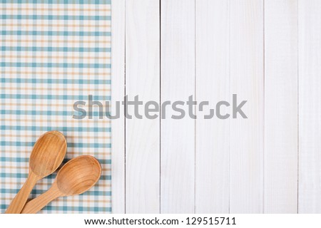 Tablecloth, wooden spoons on wood textured background - stock photo
