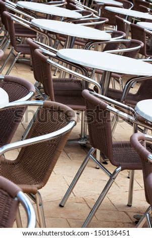 tables and chairs in a cafe on the street - stock photo