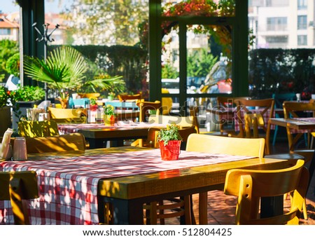 Tables and chairs in a cafe. Tablecloth in red cell and flowers in a pot for decor. Serving table in the Italian style