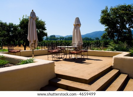 Tables and chairs next to Napa Valley vineyard in California - stock photo