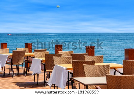 Tables and chairs on terrace in outdoor restaurant with view on Mediterranean sea in Kemer, Turkey.