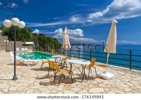 Tables and chairs standing near hotel pool under bright sunlight at Corfu, Greece - stock photo