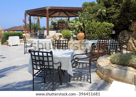 Tables and iron chairs on terrace with flower pots and beautiful garden view, Crete, Greece - stock photo