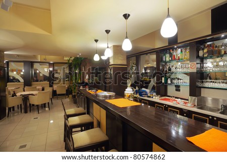 Tables, chairs, brick wall and lighting equipment of a restaurant. - stock photo