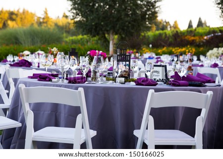 Tables, chairs, decor, and decorations at a wedding reception at an outdoor venue vineyard winery in oregon. - stock photo