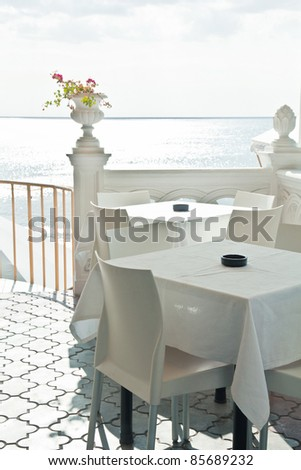Tables in a cafe on the beach - stock photo