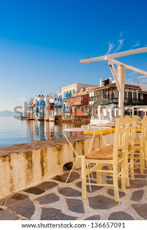 Tables  in cafe at Little Venice at sunset. Mykonos. Greece. - stock photo
